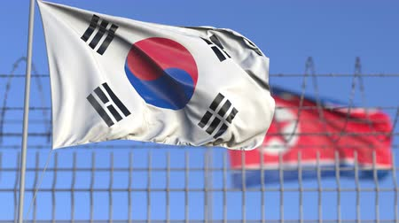 elválasztott : Waving flags of South Korea and North Korea separated by barbed wire fence. Conflict related loopable conceptual 3D animation
