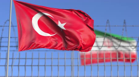 scontro : Waving flags of Turkey and Iran separated by barbed wire fence. Conflict related loopable conceptual 3D animation Filmati Stock