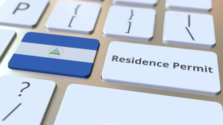 göçmen : Residence Permit text and flag of Nicaragua on the buttons on the computer keyboard. Immigration related conceptual 3D animation Stok Video