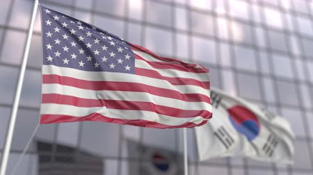 協会 : Waving flags of the United States and South Korea in front of a modern skyscraper