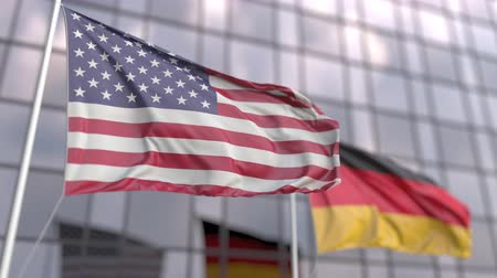 ассоциация : Waving flags of the United States and Germany in front of a modern skyscraper facade