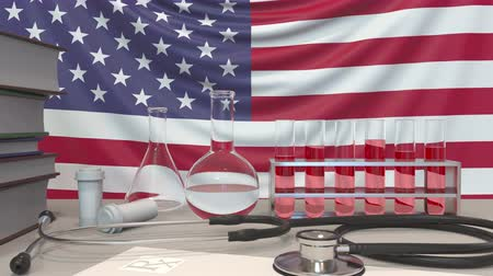 пробирка : Clinic laboratory equipment on American flag background. Healthcare and medical research in the USA related conceptual animation Стоковые видеозаписи