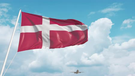 danimarka : Commercial airplane landing behind the Danish national flag. Tourism in Denmark Stok Video