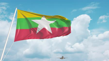mianmar : Airliner approaches the Myanma national flag. Tourism in Myanmar