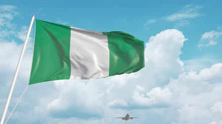 nigeria : Airliner approaches the Nigerian national flag. Tourism in Nigeria Stock Footage
