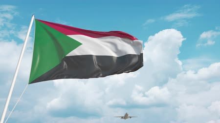 sudanian : Commercial airplane landing behind the Sudanian flag. Tourism in Sudan Stock Footage