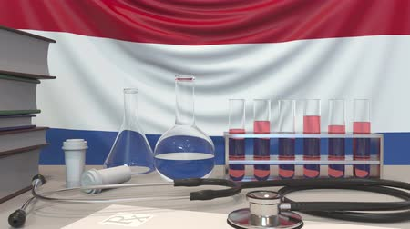 fiola : Clinic laboratory equipment on flag background. Healthcare and medical research in the Netherlands related conceptual animation Stock mozgókép