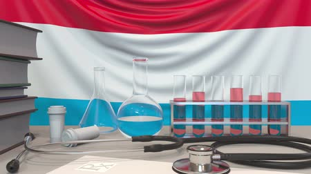 arbeidsomstandigheden : Clinic equipment on Luxembourgian flag background. Healthcare and medical research in Luxembourg related conceptual animation Stockvideo