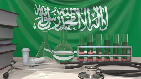 пробирка : Clinic laboratory equipment on flag background. Healthcare and medical research in Saudi Arabia related conceptual animation Стоковые видеозаписи