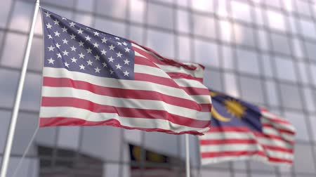 patto : Flags of the United States and Malaysia in front of a modern skyscraper facade Filmati Stock