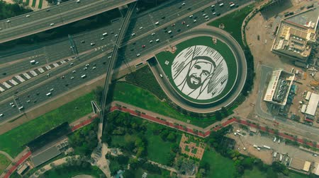 muslim leader : DUBAI, UNITED ARAB EMIRATES - DECEMBER 26, 2019. Aerial top down view of big Sheikh Zayed bin Sultan Al Nahyan portrait on the ground near highway Stock Footage