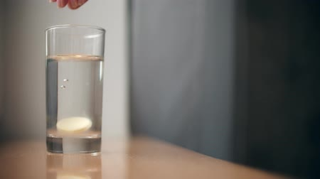 megragad : Woman puts effervescent medication or vitamin pill into glass of water