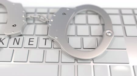 kajdanki : Handcuffs on keyboard with DARKNET text on keys. Computer crime related conceptual 3D animation