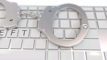kajdanki : Handcuffs on keyboard with THEFT text on keys. Computer crime related conceptual 3D animation