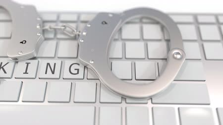 penas : Handcuffs on keyboard with HACKING text on keys. Computer crime related conceptual 3D animation