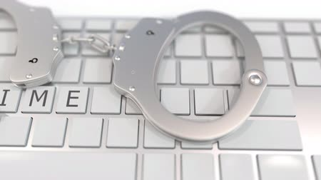 bilincs : Handcuffs on keyboard with CRIME word. Computer crime related conceptual 3D animation Stock mozgókép