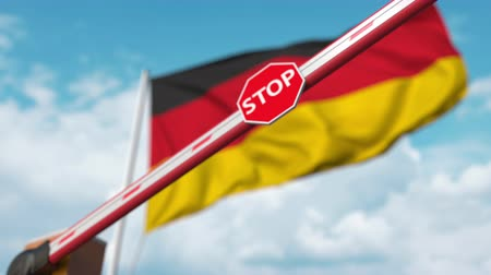 определенный : Closing boom barrier with stop sign against the German flag. Restricted entry or certain ban in Germany