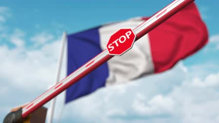 запретить : Barrier gate being closed with flag of France as a background. French restricted entry or certain ban
