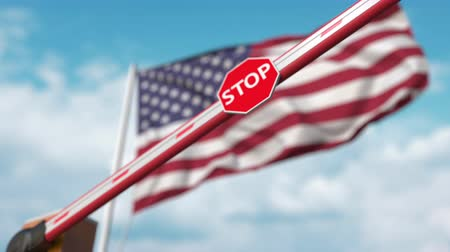 bariéra : Closing boom barrier with stop sign against the American flag. Restricted entry or certain ban in the USA
