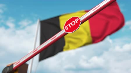 korlátozás : Barrier gate being closed with flag of Belgium as a background. Belgian restricted entry or certain ban