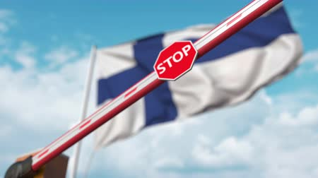 определенный : Closing boom barrier with stop sign against the Finnish flag. Restricted entry or certain ban in Finland Стоковые видеозаписи