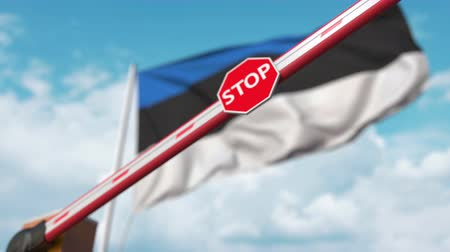 определенный : Closing boom barrier with stop sign against the Estonian flag. Restricted entry or certain ban in Estonia Стоковые видеозаписи
