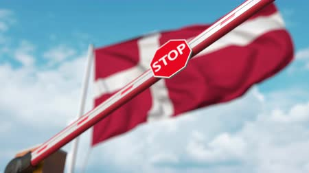 определенный : Closed boom gate on the Danish flag background. Restricted entry or certain ban in Denmark