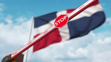 запретить : Closed boom gate on the Dominican flag background. Restricted entry or certain ban in the Dominican Republic