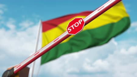 определенный : Closing boom barrier with stop sign against the Bolivian flag. Restricted entry or certain ban in Bolivia