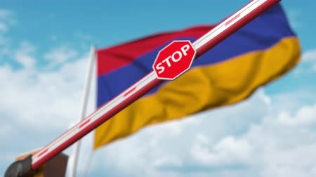 запретить : Barrier gate being closed with flag of Armenia as a background. Armenian restricted entry or certain ban