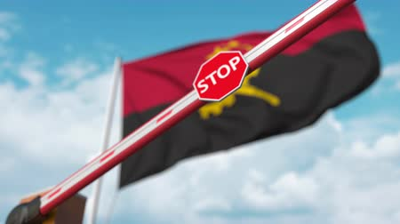 запретить : Closed boom gate on the Angolan flag background. Restricted entry or certain ban in Angola