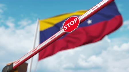 определенный : Closing boom barrier with stop sign against the Venezuelan flag. Restricted entry or certain ban in Venezuela Стоковые видеозаписи