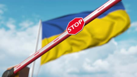 определенный : Barrier gate being closed with flag of Ukraine as a background. Ukrainian restricted border crossing or certain ban
