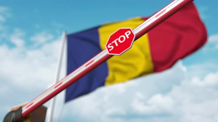 tilalom : Closed boom gate on the Romanian flag background. Restricted entry or certain ban in Romania