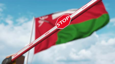 korlátozás : Closing boom barrier with stop sign against the Omani flag. Restricted entry or certain ban in Oman