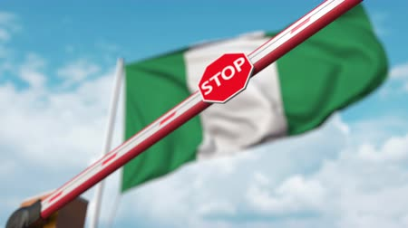 nigeria flag : Closing boom barrier with stop sign against the Nigerian flag. Restricted border crossing or certain ban in Nigeria