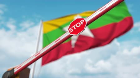определенный : Closing boom barrier with stop sign against the Myanma flag. Restricted border crossing or certain ban in Myanmar