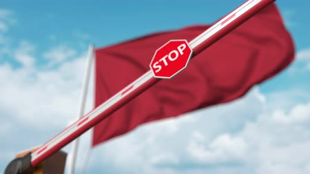 определенный : Closing boom barrier with stop sign against the Moroccan flag. Restricted border crossing or certain ban in Morocco