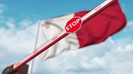 определенный : Closing boom barrier with stop sign against the Maltese flag. Restricted border crossing or certain ban in Malta