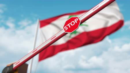 определенный : Closing boom barrier with stop sign against the Lebanonese flag. Restricted border crossing or certain ban in Lebanon