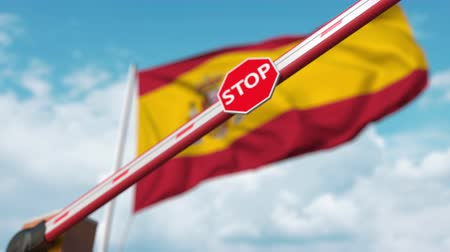 korlátozás : Barrier gate being closed with flag of Spain as a background. Spanish restricted border crossing or certain ban Stock mozgókép