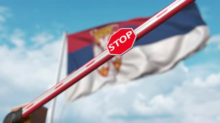 определенный : Closing boom barrier with stop sign against the Serbian flag. Restricted border crossing or certain ban in Serbia Стоковые видеозаписи
