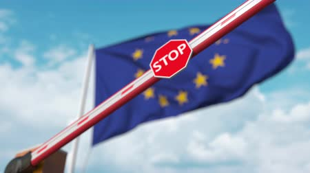 определенный : Barrier gate being closed with flag of the EU as a background. European restricted entry or certain ban