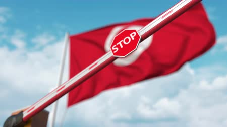 определенный : Closing boom barrier with stop sign against the Tunisian flag. Restricted border crossing or certain ban in Tunisia