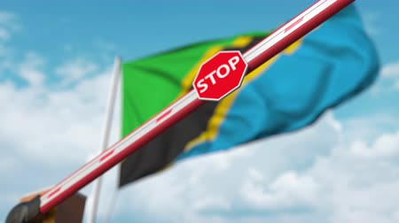 определенный : Closing boom barrier with stop sign against the Tanzanian flag. Restricted border crossing or certain ban in Tanzania