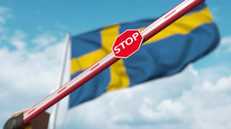 korlátozás : Closing boom barrier with stop sign against the Swedish flag. Restricted border crossing or certain ban in Sweden