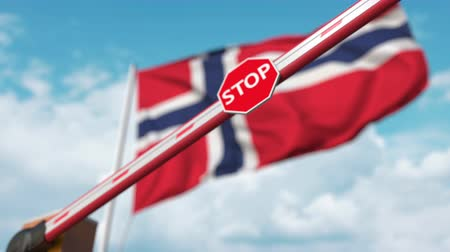 запретить : Barrier gate being closed with flag of Norway as a background. Norwegian restricted entry or certain ban Стоковые видеозаписи