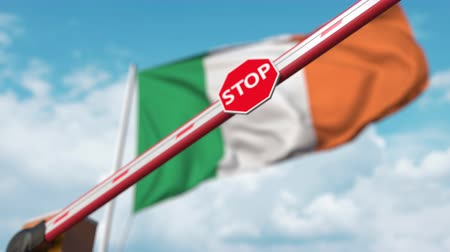 определенный : Closed boom gate on the Irish flag background. Restricted entry or certain ban in Ireland