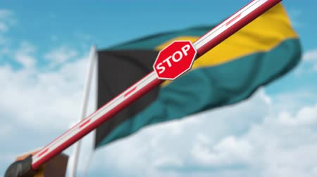 определенный : Closed boom gate on the Bahamian flag background. Restricted entry or certain ban in the Bahamas