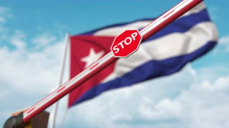 определенный : Closing boom barrier with stop sign against the Cuban flag. Restricted entry or certain ban in Cuba Стоковые видеозаписи